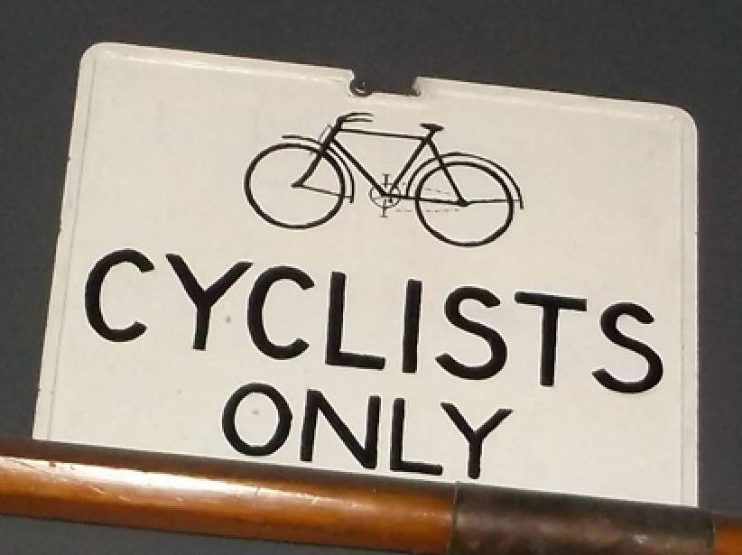 White sign saying 'Cyclists Only' with an image of a bicycle on it