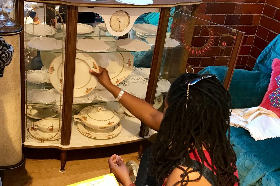Actor and storyteller Amantha Edmead putting in decorative plates into a glass cabinet, as part of creating the West Indian/Caribbean living room installation.