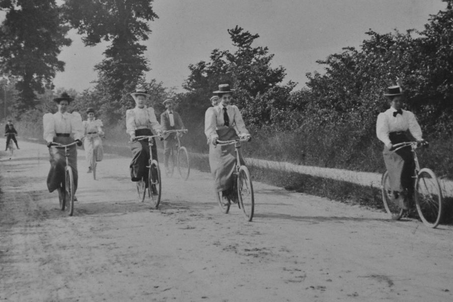 Black and white photograph of 4 women and 3 men on bicycles, wearing Victorian clothing