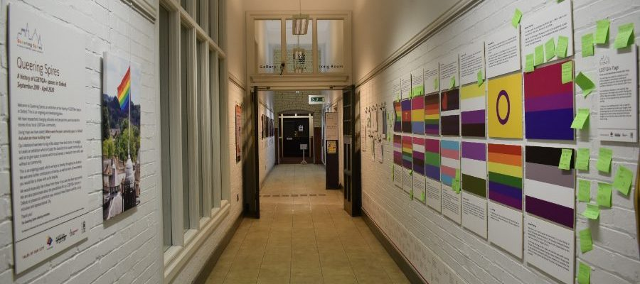 Display of various LGBTIQA+ flags with descriptions and visitors' comments on post-it notes, and a panel introducing the exhibition with a photo of the rainbow flag on Radcliffe Camera