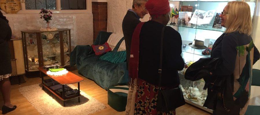 Three people talk inside a recreated West Indian/Caribbean living room, in front of a glass case with historical objects representing Oxford's Windrush community