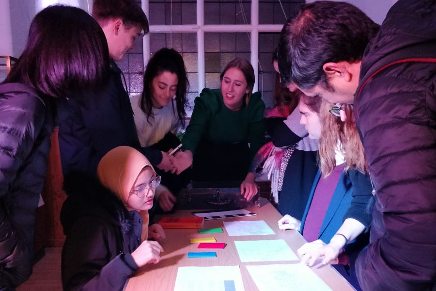 Group of young people around a table in an Escape Room in the Museum, 2019