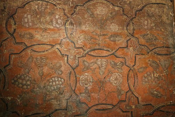 A section of wall painting. It shows floral designs within various segments.