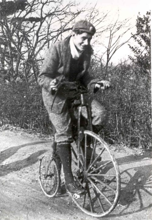 A black and white photograph of a young man (William Morris) on a penny-farthing