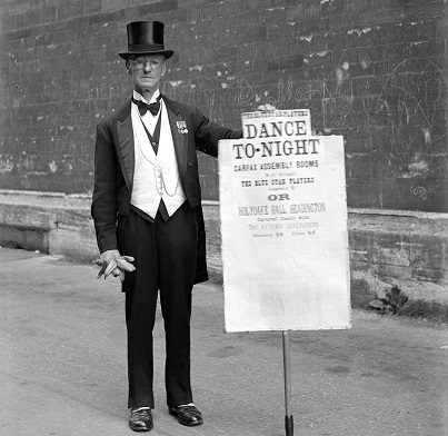 A black and white photograph of an older man wearing a suit and top hat holding a board advertising an upcoming dance