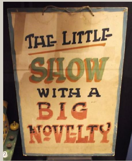 A large sign with the words 'The little show with a big novelty' in colourful writing