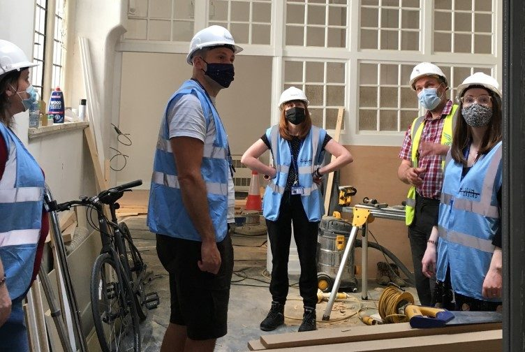 Photograph of museum team in hard hats and masks looking at the new museum space