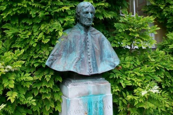 Copper bust of Cardinal Newman surrounded by a green bush