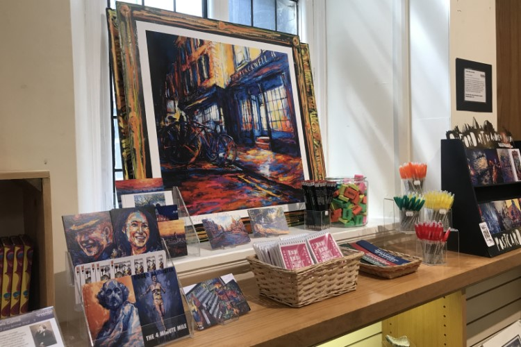Items on display in the gift shop including prints by Andrew Manson