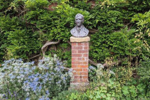 Bust of Cardinal Newman surrounded by a green bush