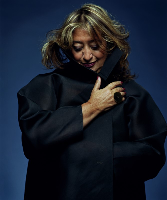 Photograph of Zaha Hadid dressed in black and looking down