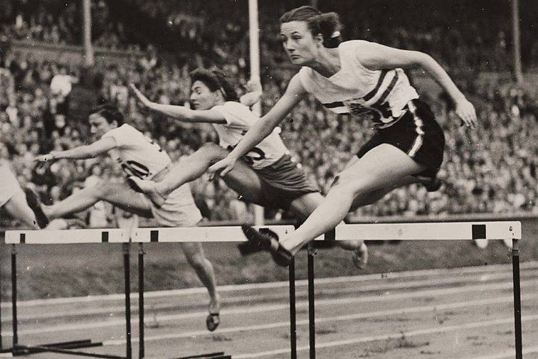 Black and white photo of young women jumping the hurdles at the Olympic Games
