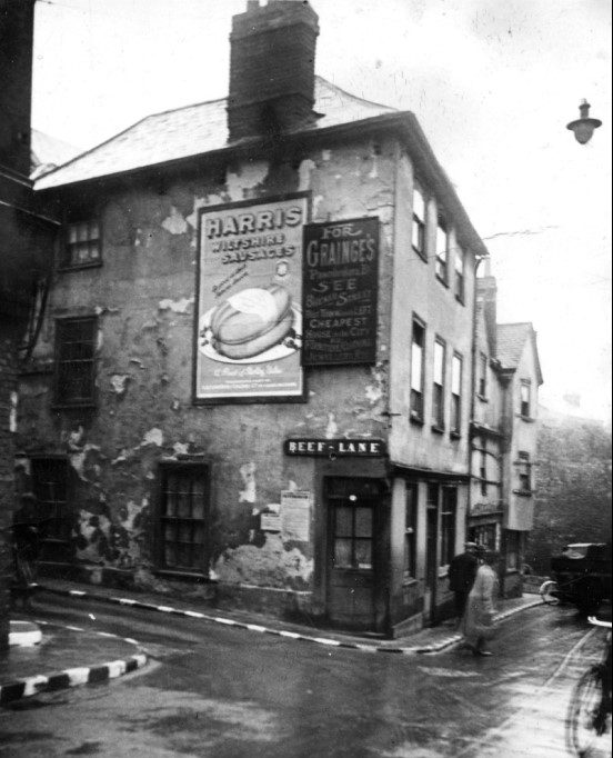 Black and white photograph showing a shabby looking building on the corner with ads for local businesses