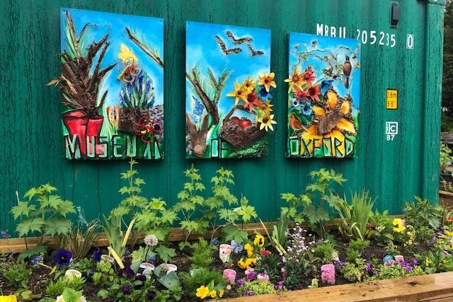 Museum of Oxford sensory garden. Colourful artwork above a bed filled with different flowers.