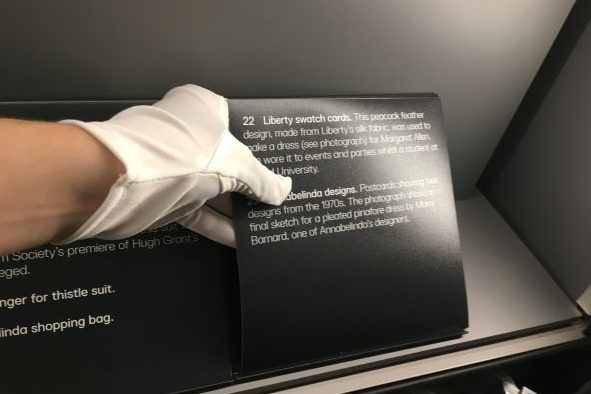 Gloved hand installing a museum label
