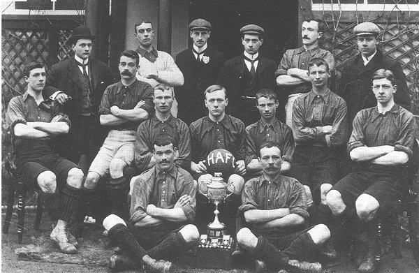 Black and white photograph of Headington United with a trophy. Featuring 15 white men in football kit of the period and some in suits.