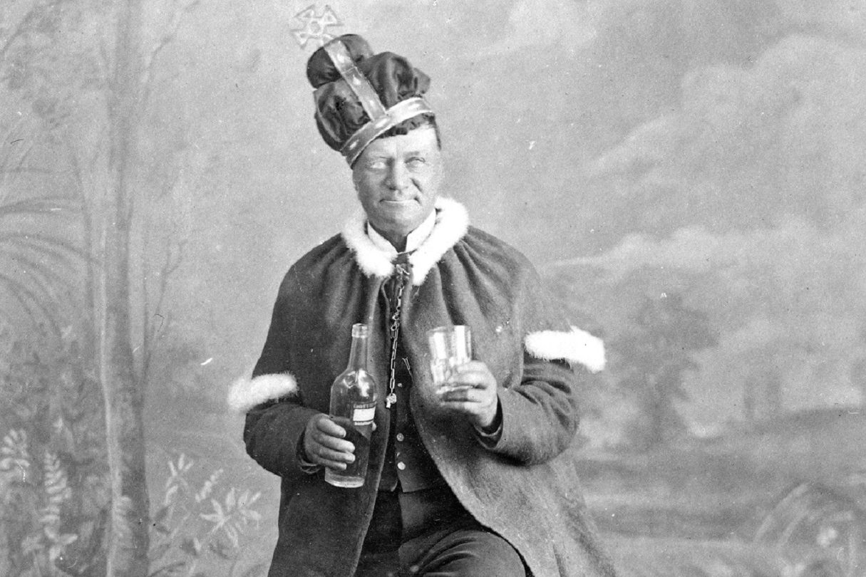 Black and white photograph of a man with a lopsided crown on his head, holding a glass and a bottle and wearing a robe
