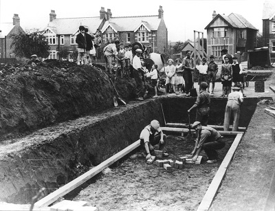 A black and white photograph of an ARP shelter being built on Windmill Road in Headington
